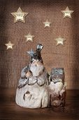 stock photo of figurine  - christmas card with vintage santa clay figurine on wooden and canvas background - JPG
