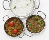 A bowl of spiced lamb curry with coriander leaves and slivers of red and green chillies, next to a bowl of Lahore-style lamb curry with split peas and some basmati rice. from above
