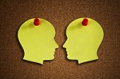 Head shape paper note reminder with thumb tack pin on cork board concept for face off, health care, dementia, memory, discussion and business meeting