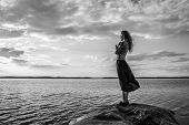 image of jeans skirt  - Beautiful young woman looks at the horizon on shore wind blowing and cloudy sky  - JPG