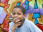 stock photo of hair integrations  - Young Afro boy in front of a graffiti wall - JPG