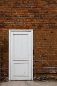 White Wooden Door On An Old Brick Wall.