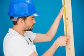 Carpenter or builder wearing a hardhat concentrating as he measures a plank of wood with a tape measure, blue background