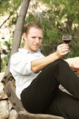 young happy white caucasion man taste and enjoy red wine outdoor in in countryside . classic style f