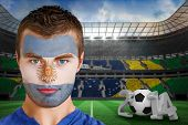 Composite image of serious young argentina fan with face paint against large football stadium with b