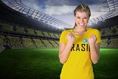 Excited football fan in brasil tshirt in a large football stadium with fans in yellow