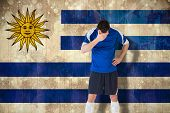 Disappointed football player looking down against uruguay flag in grunge effect