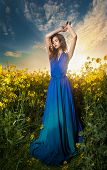 Fashion beautiful young woman in blue dress posing outdoor with cloudy dramatic sky in background