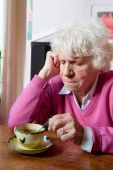 Depressed Elderly Woman Sitting At The Table