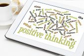positive thinking and attitude word cloud on a white digital tablet with a cup of coffee