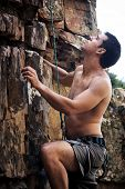 An attractive man with no shirt on rock climbing