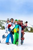 Cheerful friends standing with snowboards