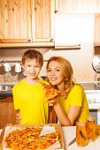 Smiling boy and his mother with pizza slice