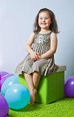 Little Girl Sitting On Cube