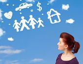 picture of daydreaming  - Young girl daydreaming with family and household clouds on blue sky - JPG