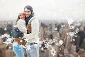 Young winter couple against city skyline
