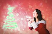 Pretty girl in santa outfit blowing against red abstract light spot design