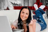 Woman ordering shopping from online against blurry christmas tree in room