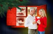 Loving couple with gift against festive fir branch with baubles
