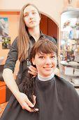 creating hairstyles hairdresser at salon. indoor shot
