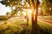 foto of swing  - Young kissing couple under big tree with swing at sunset - JPG