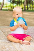 Cute baby sitting on a sand and drinking