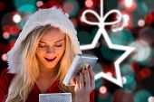 Sexy santa girl opening gift against blurred christmas background