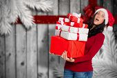 Woman holding many christmas presents against festive bow over wood