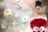 Pretty santa girl presenting with hands against blurred christmas background