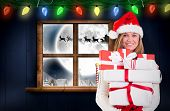 Festive blonde holding pile of gifts against santa delivery presents to village