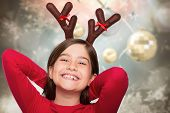 Festive little girl wearing antlers against blurred christmas background
