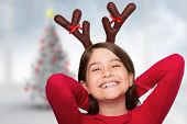 Festive little girl wearing antlers against blurry christmas tree in room