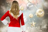 Pretty girl in santa outfit holding gift against blurred christmas background