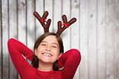 Festive little girl wearing antlers against blurred wooden planks