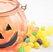 Halloween Pumpkin Glass With Jelly Beans Drop Isolated