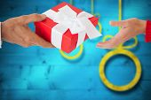Couple holding gift against blurred christmas background
