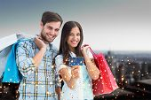 Couple with shopping bags and credit card against high angle view of city skyline