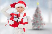 Festive woman holding gifts against blurry christmas tree in room