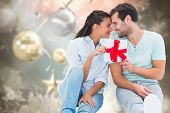 Young couple holding gift against blurred christmas background