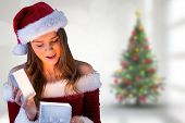 Pretty santa girl opening gift against blurry christmas tree in room