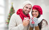 Winter couple holding mugs against blurry christmas tree in room
