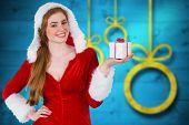 Pretty girl in santa costume holding gift box against blurred christmas background