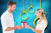 Young couple with gift against blurred christmas background