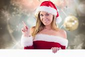 Festive blonde smiling and pointing against blurred christmas background