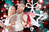 Happy couple with shopping bags and tablet pc against blurred christmas background