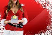 Sexy santa girl holding gift against christmas themed snow flake frame