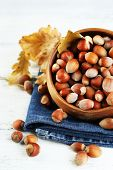 Hazelnuts on plate on napkin on wooden background