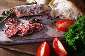 French salami with tomatoes, parsley and bread on cutting board on wooden background