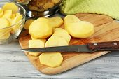 Raw peeled and sliced potatoes  on cutting board, on color wooden background