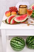 Composition of ripe watermelon, fruits, pink wine in glass and wooden barrel on  color wooden table, on light background